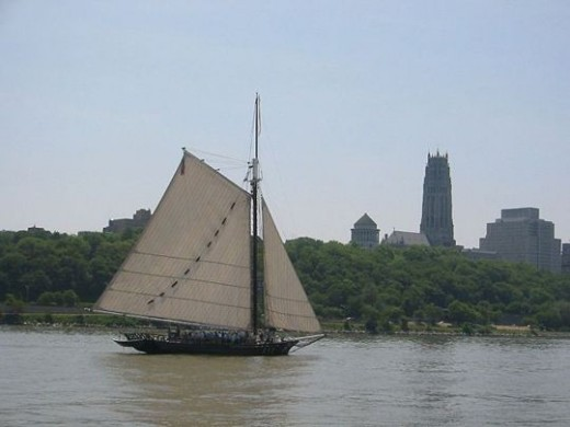 Photo of the sloop Clearwater sailing south on the Hudson River, past Manhattan's Grant's Tomb and Riverside Church
