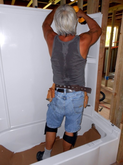 My husband installing the tub and tub surround.