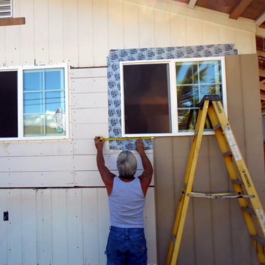 New T111 plank siding is going on the outside of the cottage. Notice wrappings around the new window frames BEFORE siding goes up.