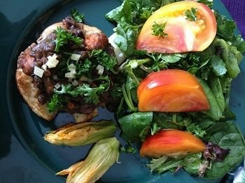 Black bean ragout over baked potato with green salad and squash blossoms