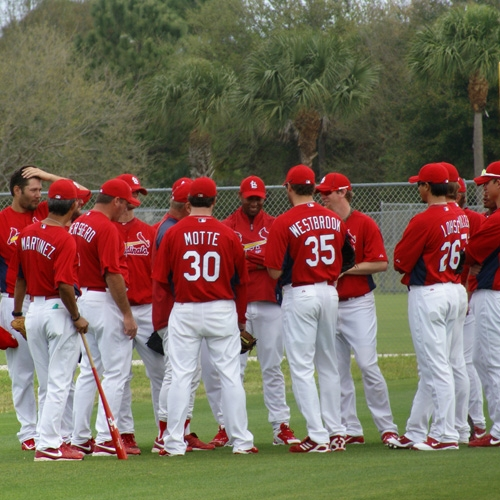 Pitchers gather round for instructions prior to the start of pitching practice.