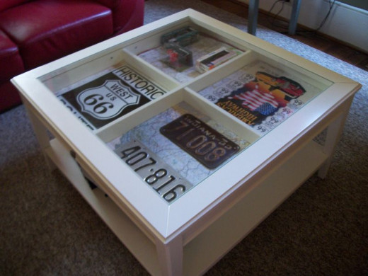 Route 66 tin signs and other memorabilia are displayed in this shadow box coffee table.