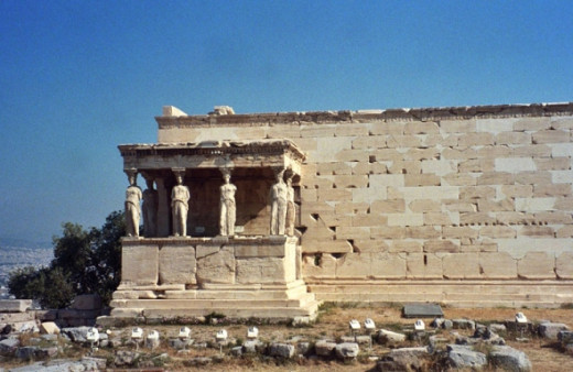 "South side of the Erechtheion, ""Porch of the Maidens,"" facing the Parthenon. The karyatids (human-shaped-columns) are replicas; the originals are in museums to protect them."