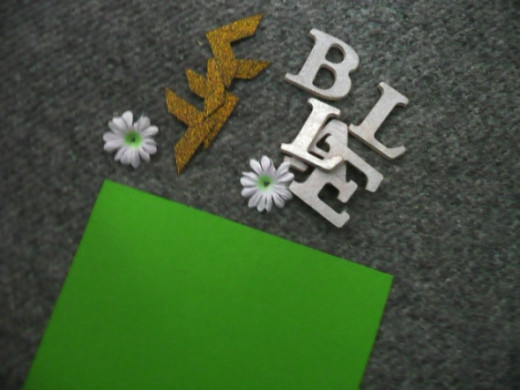 Green cardstock, silver chipboard letters B-E-L-L-A, photo corners, pink Gerbera daisy and white daisy fabric flowers (I used white ones to match the white daisies on the paper I used, but you can use just pink, green or yellow to match those on the