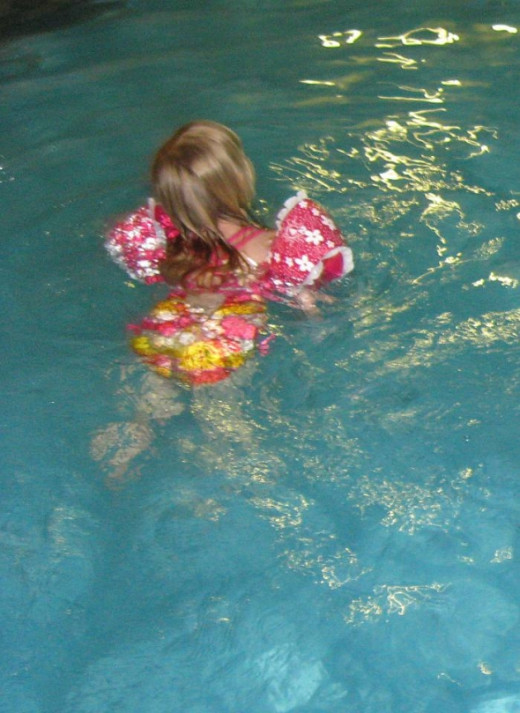 swimming with the floaties on and having lots of fun!