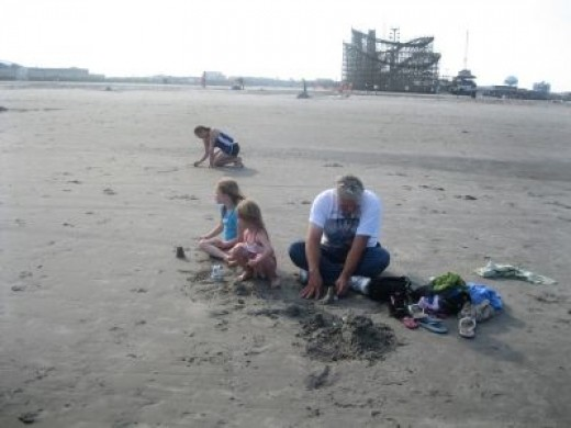 Dad Helping His Girls Make a Sandcastle