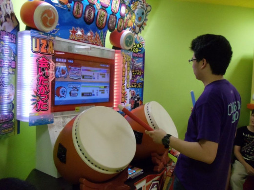 Another one of my friends at the arcade taking turns with the host family playing a video game.
