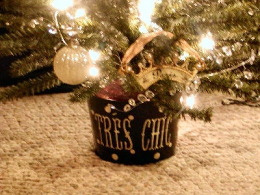 """I found a small black pail with """"Tres Chic"""" on it in white (on clearance at a craft/home décor store) and used it as the holder for this 3 foot tree. I found a gold and white crown ornament with a ribbon and the word """"Paris"""" on it at craft store."""