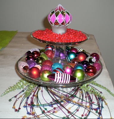 Two cake stands, stacked. Top cake stand has red hots surrounding an ornament upside down in a votive holder. Bottom plate has an assortment of ornaments.
