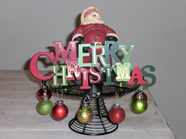 """Santa holding a """"Merry Christmas"""" sign on the black wire cake stand."""