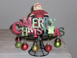 "Santa holding a ""Merry Christmas"" sign on the black wire cake stand."
