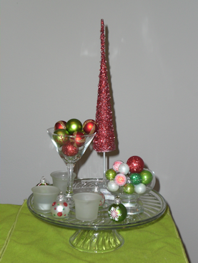 Glass cake plate with tree figurine, martini glass and small glass bowl filled with ornaments, votives and ornaments scattered.