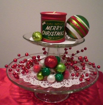 Two cake stands stacked. Top stand has 2 ornaments and a candle, bottom stand has wired berries and ornaments. Both stands are using doilies.