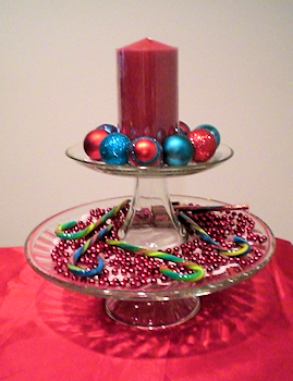 """Stacked cake stands with 6"""" pillar candle surrounded by small ornaments on top and bead garland with candy canes on the bottom layer."""