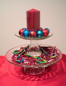 "Stacked cake stands with 6"" pillar candle surrounded by small ornaments on top and bead garland with candy canes on the bottom layer."