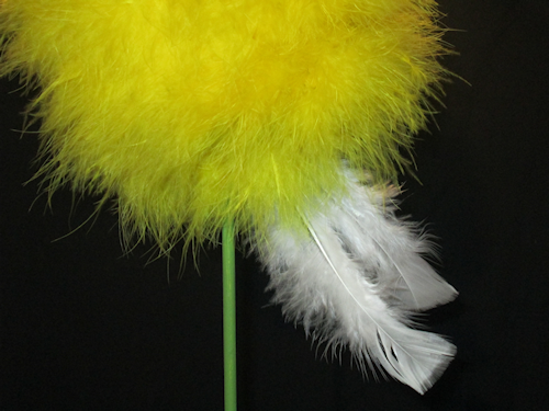 At the base of the yellow ball, right next to the dowel rod, add a feather. Move a little and add another. Keeping working until you have a line of feathers around the middle perimeter of the yellow ball.