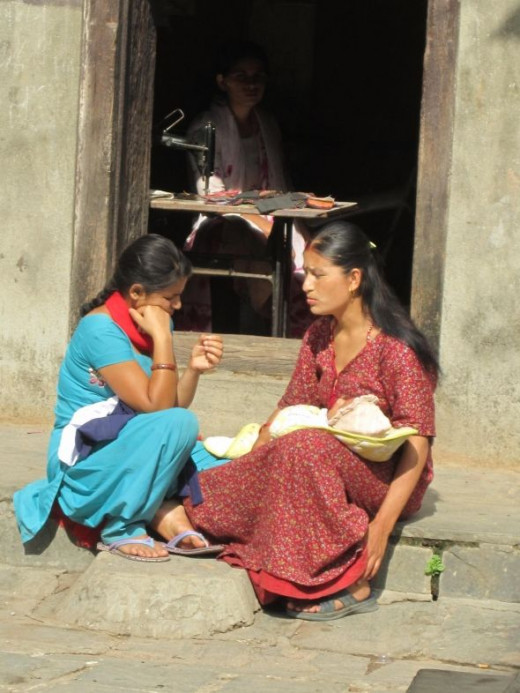 Two women, a baby and a tailor in Thamel, Kathmandu