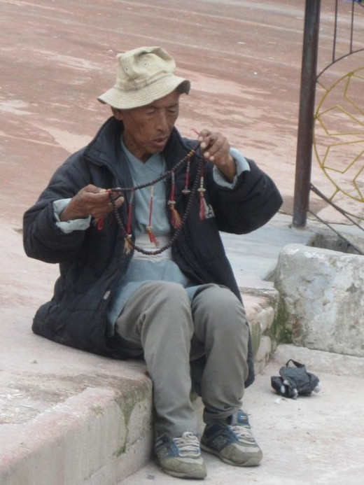 A man studies his prayer beads at Boudha Stupa