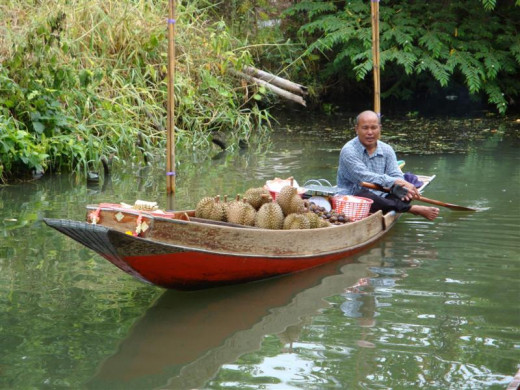 A Thai durian vendor selling his precious durian and mangosteen fruits from a small boat along one of the many water-ways of Thailand.