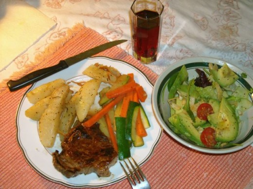 Panbroiled steak dinner, oven-roasted potatoes, mixed fresh vegetables ... and salad with avocado slices.