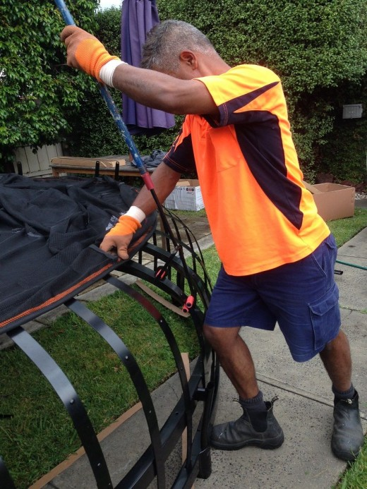 Charles, the installer, is using a special tool that bends the metal strips so he can attach them to the trampoline mat