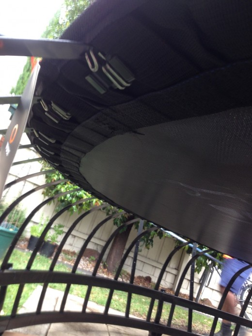Under the trampoline mat - a hook attaches to each metal strip. Then, safety rings are attached after that. Great design.