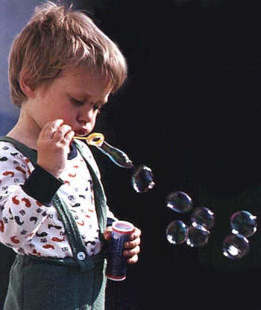 Boy blowing soap bubbles