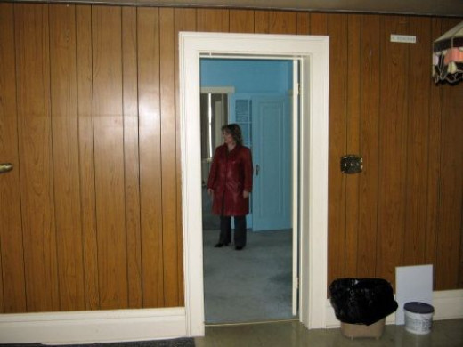View of paneling in kitchen on one wall. That is Lana surveying the living room.