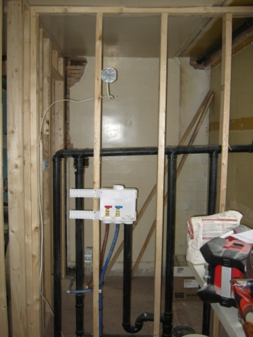 The framing that separates the laundry room and the powder room. You can see the hook ups for the future laundry facilities.