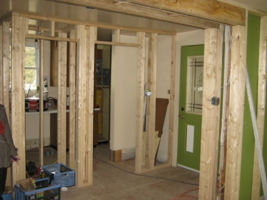View of the front entrance, closet and laundry entrance from kitchen.