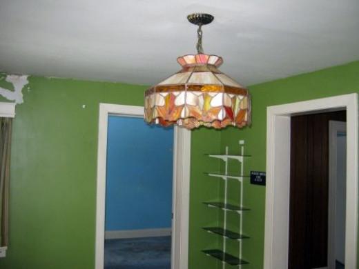 Old lighting fixture in living room. View towards doorways to kitchen (right) and living room (left).