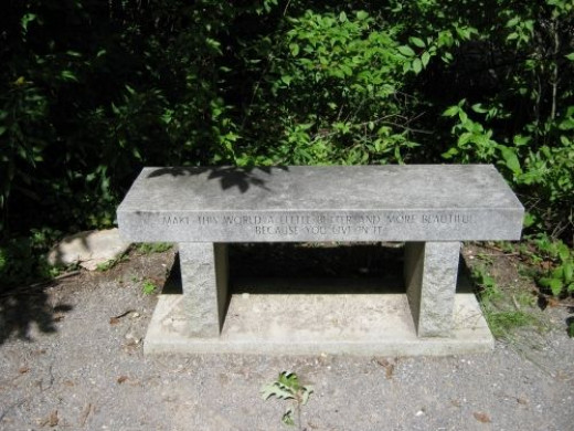 """Donated bench beside boulder inscribed with, """"Make this world a little better and more beautiful because you live in it."""""""