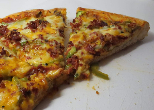 A package of Dunn's smoked meat, a mild tomato sauce, half a green pepper and a couple sliced mushrooms. Moz, cheddar, romano cheeses.