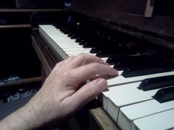 Hand is leaning on edge piano and arm is too low. Not good for Piano Playing