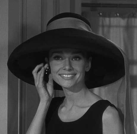 Audrey Hepburn again with a long scarf tied around a large brimmed hat.