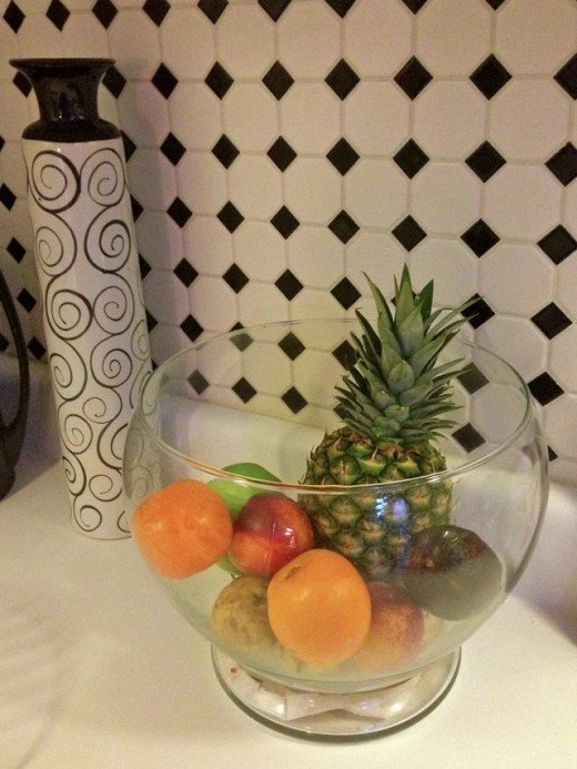 A glass bowl holds fruit. It's decorative and seems to 'disappear' giving the illusion of space
