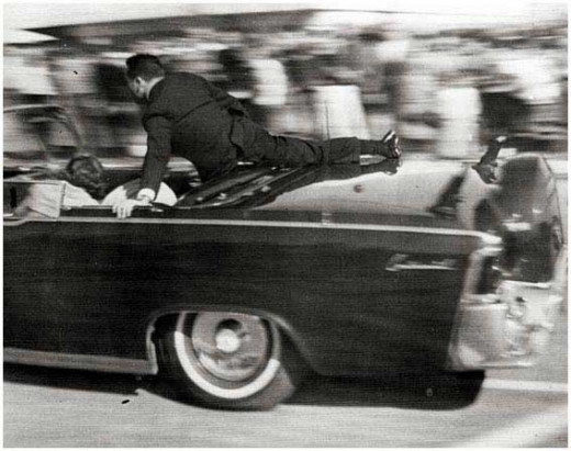 A secret serviceman leaps onto the trunk of the limousine seconds after the shooting.