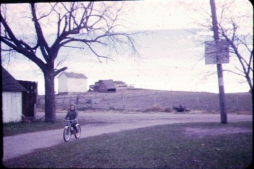 Photo of the Iowa Farm - Garage on left; Corn crib on hill. Brother on bicycle.