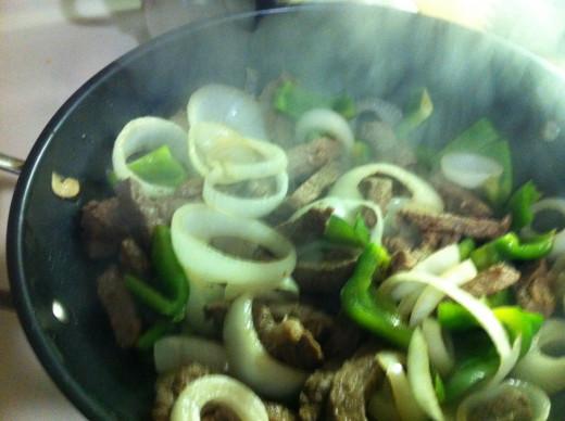 Add the steak back into the wok, stir to heat.