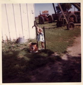 About 1962, my oldest daughter on the farm attempting to get a drink from the faucet into the old tin up that always hung on the steel post!  ;-)