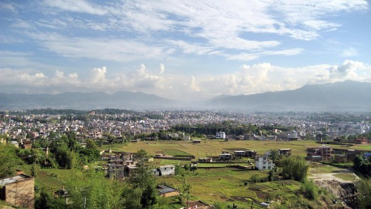 A view of Kathmandu City nestled in Kathmandu Valley with the Himalayan Mountains in the background.  Originallly produced by aNantaB and distributed under Creative Commons Attribution 2.0 License.