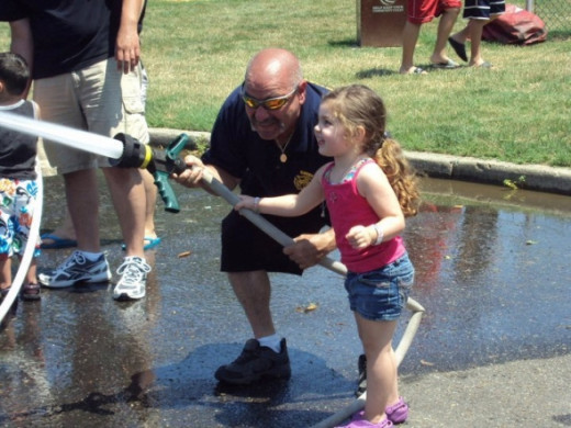 "Every firefighter knows you have to break the rookies in early and our families are always ready to grab a handline, gear up and go team, go! Picture of Fire Chief Barry Rashkin and his granddaughter ""manning"" the attack handline."