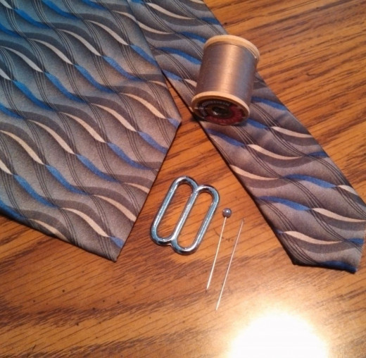 Gather your materials: 1 necktie, 1 triglide, scissors, stick pin, sewing needle, coordinating thread.