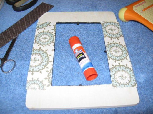Bring in the paper scraps to cover the frame. Fabric, ribbon or stickers would work well, too.
