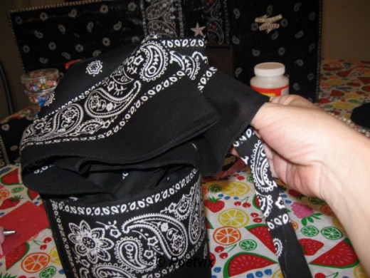 Insert the newly fashioned drawstring into the top fold of the bandanna you just glued down.