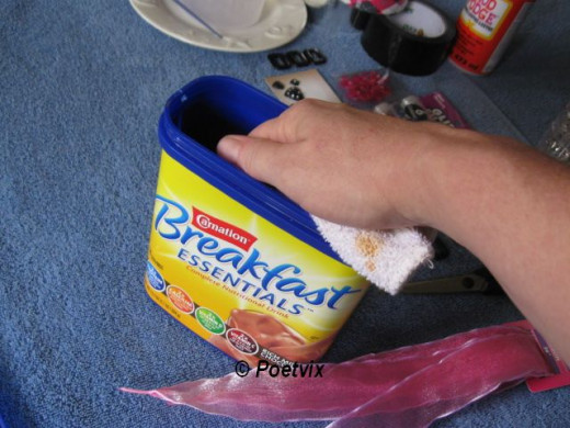 Wash out the inside of the Carnation Instant Breakfast container, or whatever plastic, hard bottom item you want. Just be sure it has a lid so you can close the purse and keep all of your stuff safe and dry. Mine still smells like chocolate after bei