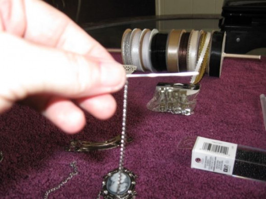Insert the wire through the chain and then through the back of the barrette back.  Twist off and bend it over the back.