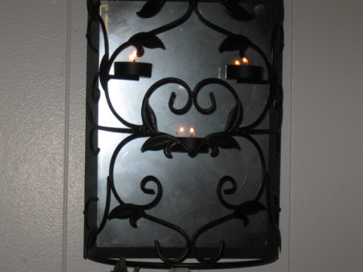 Wrought iron tea light mirror backed holder.