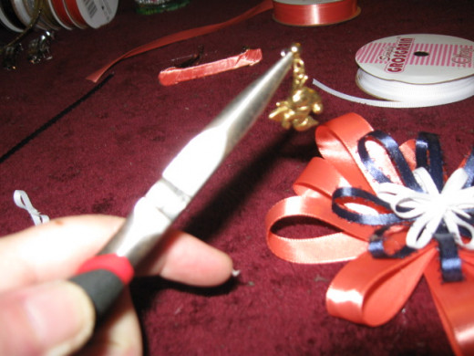 Bend the earring post to make a loop around the last smallest ribbon before gluing it down.