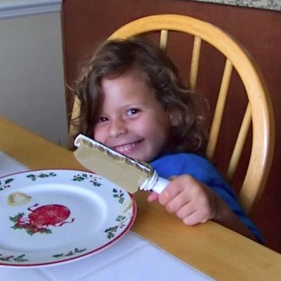 My daughter at breakfast, complete with bed head and a smile